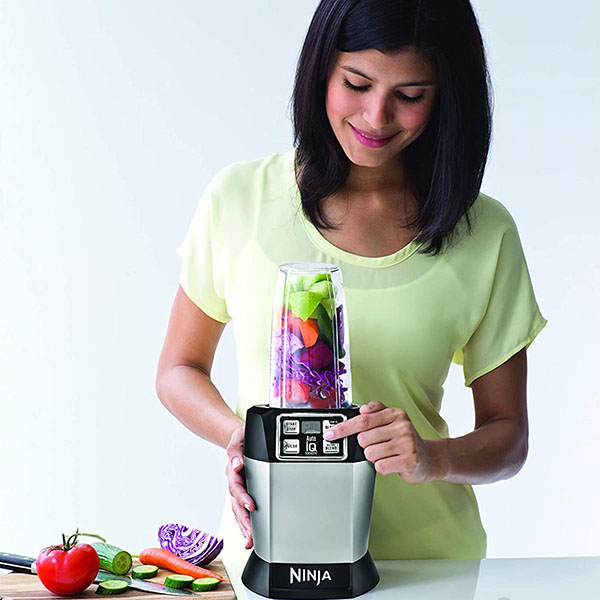 A lady using the Ninja BL480D Auto iQ to blend vegetables and fruits