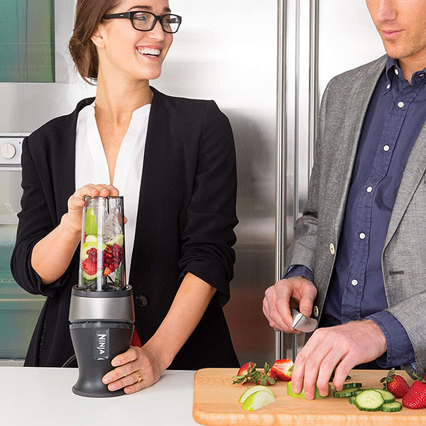 A couple doing food preparation using Ninja Personal Blender