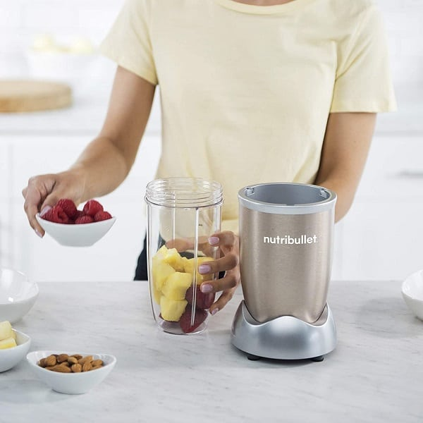 A person putting fruits on the blender jar to be crushed using the Nutribullet 900 Pro
