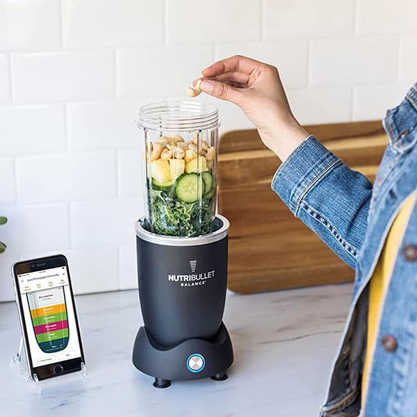 A lady using the NutriBullet Balance to blend fruits and vegetables