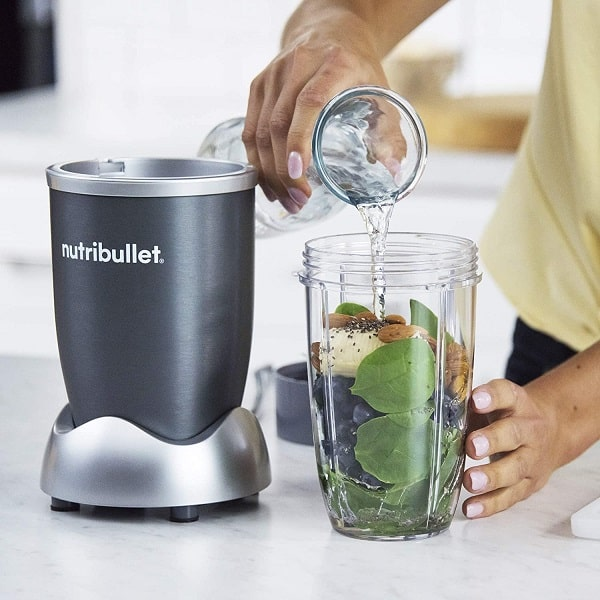 A woman using the NutriBullet 600 to make a smoothie