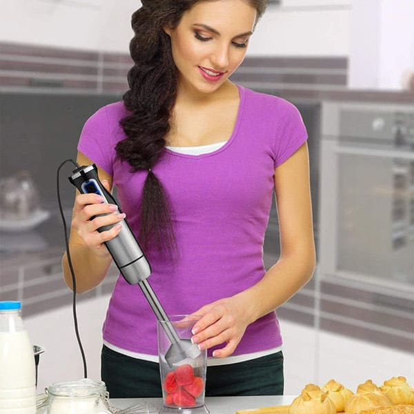 A woman using one of the Best Immersion Blender to blend strawberries