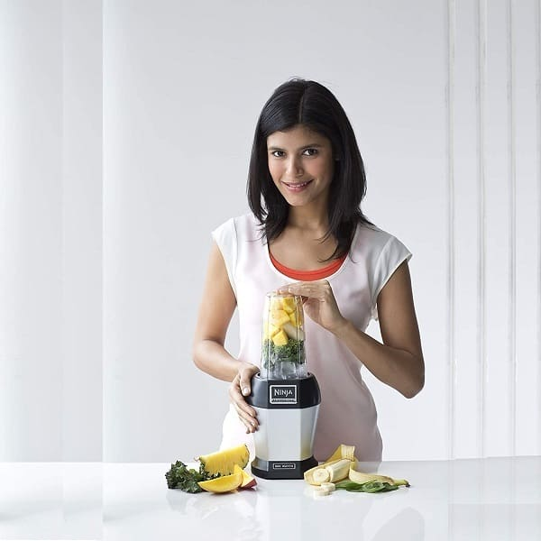 A woman using one of the best blender for protein shakes to blend fruits