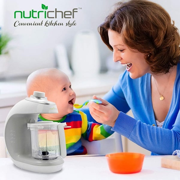 A mom feeding her infant with baby food using one of the Best Baby Food Maker and Blender in 2021