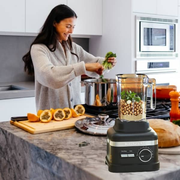 A smiling woman cooking her favorite dish using one of the best Kitchenaid Blenders as a kitchen aid