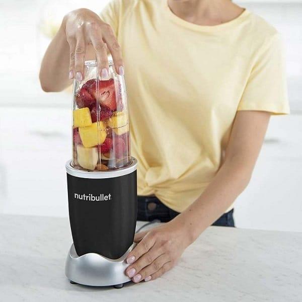A woman using NutriBullet Blender making fruits smoothie