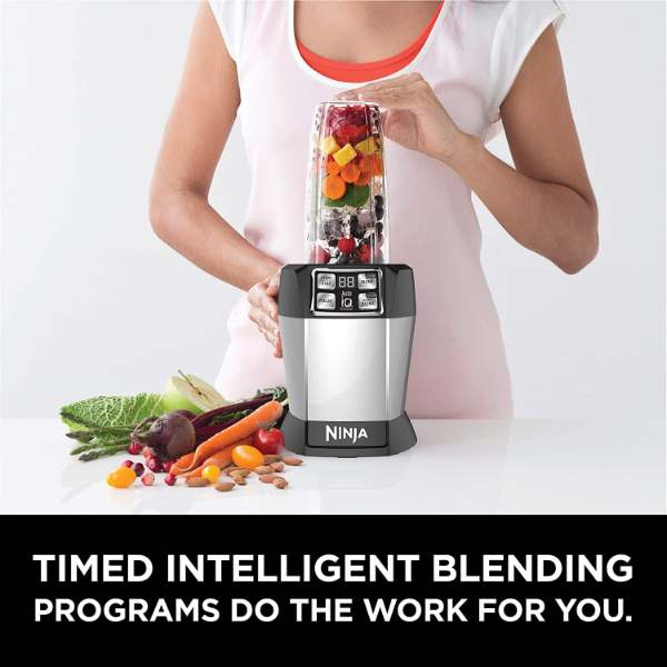 A woman using the Ninja BL480D blender to make a smoothie
