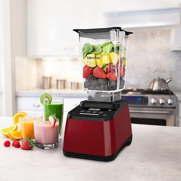 Fruits and a glass of smoothie beside a Blendtec 625 Blender