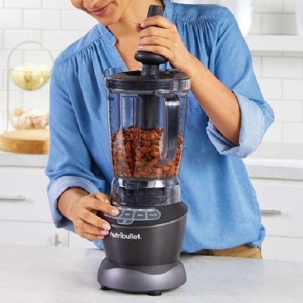 A woman in blue blouse that looks like lectruring how to use a ninja blender