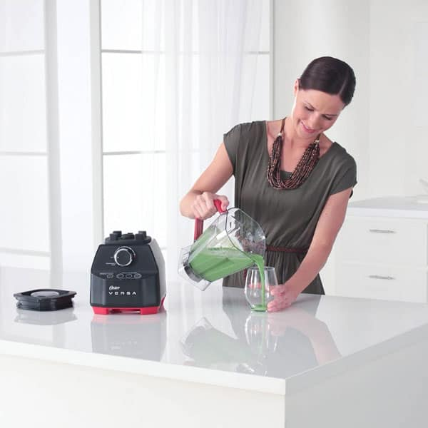 A lady pouring out smoothie from Oster Versa 1400 blender jar